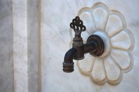 Detail of a water tap valve twist marble walls. Banco de Imagens