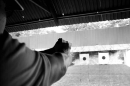 Blurry A man holding a gun in hand ready to shooting practice at targets paper. Black and white image.