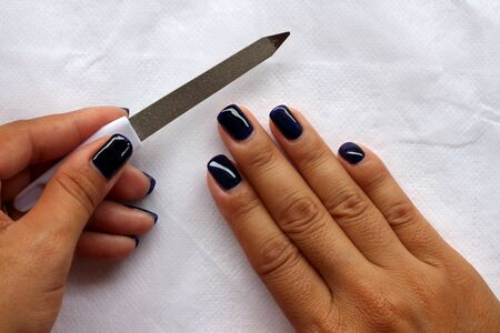 Nail file doing manicure. Woman beautiful nail care.