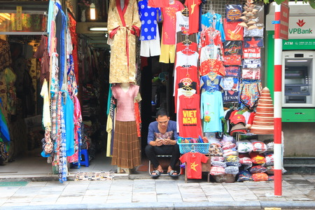 quater: HANOI, VIETNAM, SEPTEMBER 18, 2015 : Seller reading book in front of clothes shop in Old quater