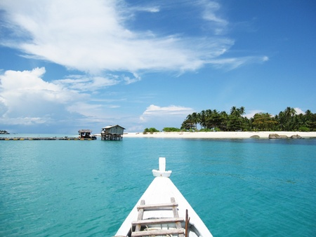 A boat is heading on the crystal sea to the paradise beach