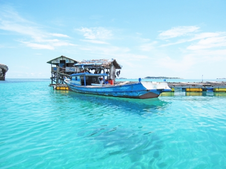 Fishing boat is floating on a very clear sea