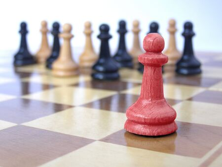 differentiate: team of pawns with red leader  Stock Photo