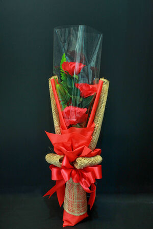 Red rose bouquet with bow tie on black background photo