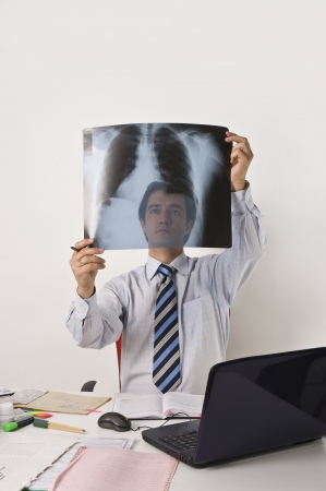 Young man working on table with computer, documents, x-ray pictures, clinical diagrams, prescriptions Professional clinical research monitor at working place
