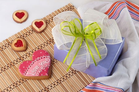 Decorated with inscription heart-shaped biscuits for Valentines Day and gift box with a bow photo