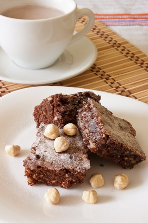 powdered sugar: Delicious chocolate brownie and hazelnuts sprinkled with powdered sugar