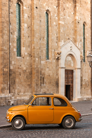 60 64 years: Classic Orange Italian Car in Front of a Catholic Church Stock Photo