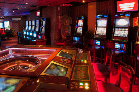 casino table: Roulette table and Slot machine. Red lighted casino. Stock Photo