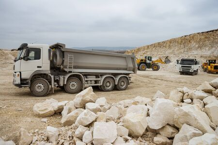 Heavy Trucks and bulldozers in Stone Pit. Focus on Front Truck, large rocks at front and yellow bulldozer and truck at background