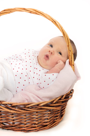0 3 months: Cute baby in basket. Looking at camera