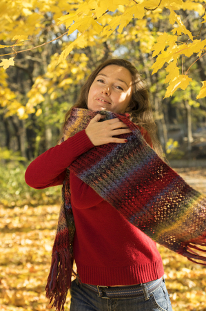 between 30 and 40 years: Woman with brown hair at autumn forest. Hug with a multicolored scarf