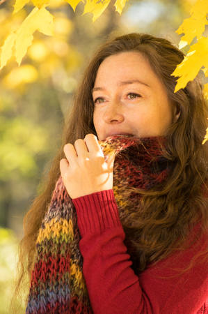 between 30 and 40 years: Woman with brown hair at autumn forest. Dressed with red sweater and multicolored scarf.