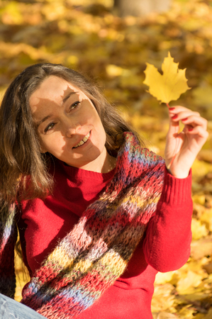 between 30 and 40 years: Woman with brown hair at autumn forest holding a yellow maple leaf with shadow on the face