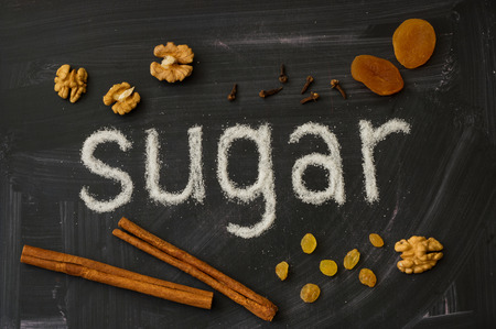 describe: Word made of sugar describe SUGAR, decorated with spices, cinnamon, raisin and walnuts Stock Photo
