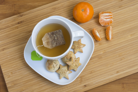 Winter tea breakfast with cookies and tangerines on wooden background