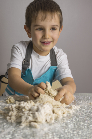 Little boy is kneading raw pizza dough and smiling Reklamní fotografie