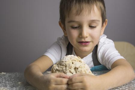 Little boy is kneading raw pizza dough and making a hug Reklamní fotografie