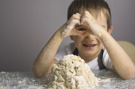 Little boy is kneading raw pizza dough and looking through heart shape hands Reklamní fotografie