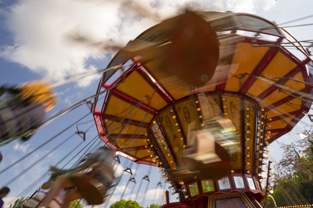 Chain swing carousel ride at a carnival with motion blur during sunset Stock Photo
