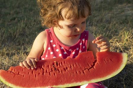 Little girl eating giant slice of ripe summer watermelon Reklamní fotografie