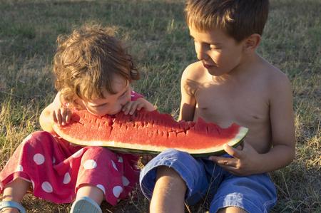 Little girl and boy eating giant slice of ripe summer watermelon, sitting on the grass at sunset Reklamní fotografie