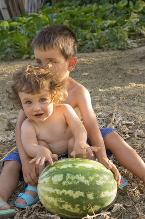Brother and sister sitting in the meadow with giant watermelon