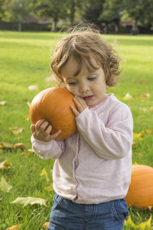 Adorable girl toddler embracing pumpkins on an autumn field