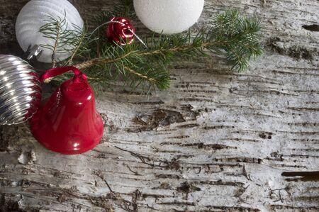 Wood bark background with christmas decoration, pine branch, balls and bells Reklamní fotografie