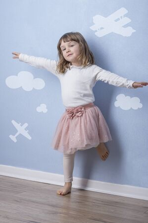 Happy little girl having fun on blue background with simple graphics. The imaginative concept for freedom, growth, future.