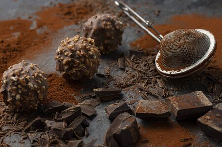 Homemade dark chocolate and nuts truffles surrounded by chocolate pieces and cocoa powder