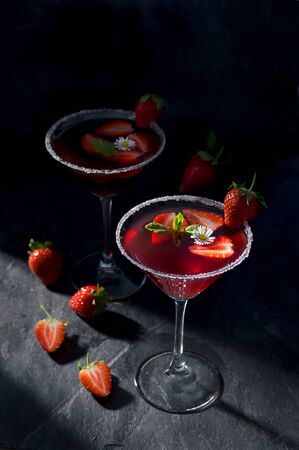 Fresh strawberry cocktail in a martini glass on dark stone background, decorated with fresh fruits, mint and a small flower. Copy space on top.