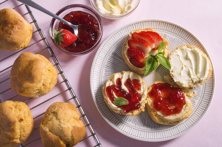 Tasty breakfast of scones with clotted cream and strawberry jam on pink background, top view