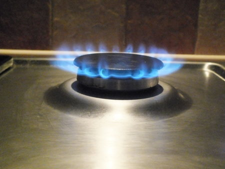 homestyle: A gas burner on a hob lit giving a distinct blue flame Stock Photo