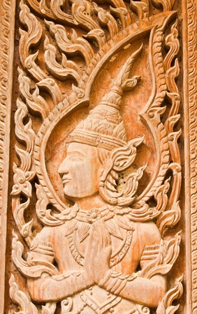 The old traditional Thai art wood carvings on a door in a temple  Wat Liab ,NAKORNRATCHASIMA,THAILAND photo