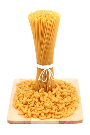 Spaghetti and macaroni on wooden board photo