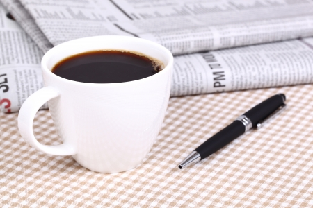 Fresh hot coffee on newspaper with pen photo