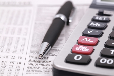 Newspaper stock information with pen and calculator Stock Photo - 17998781