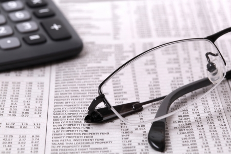 mutual fund: Newspaper stock information with calculator and glasses Stock Photo
