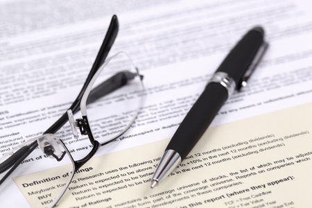 Eye glasses and document with pen close up photo