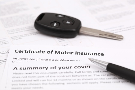 Certificate of motor insurance with car key and pen Stock Photo