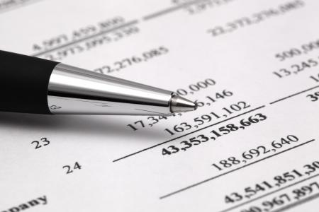 bifocals: Reading finance report with pen Stock Photo