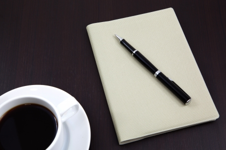 notebook with coffee cup on table photo
