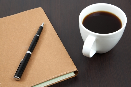 Cup of coffee on a wooden table with book and pen photo