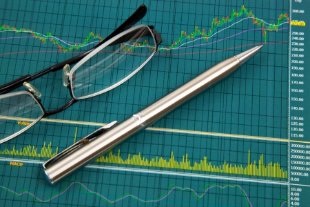 A pen and spectacles on the Stock chart and financial report