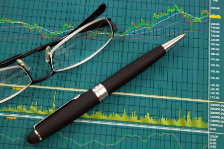 A pen and spectacles on the Stock chart and financial report photo