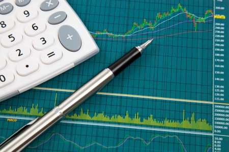 A pen and calculator on the Stock chart and financial report