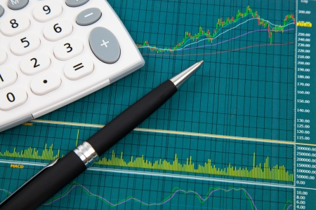 A pen and calculator on the Stock chart and financial report photo