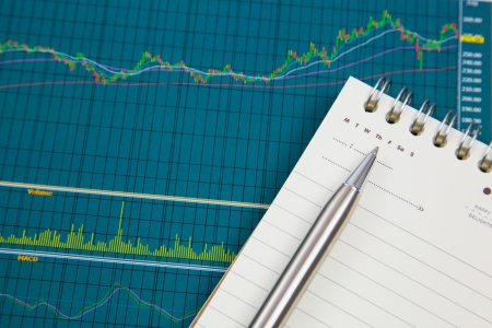 A pen and notepad on the Stock chart and financial report