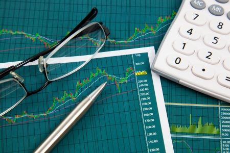 A pen, calculator and spectacles on the Stock chart and financial report